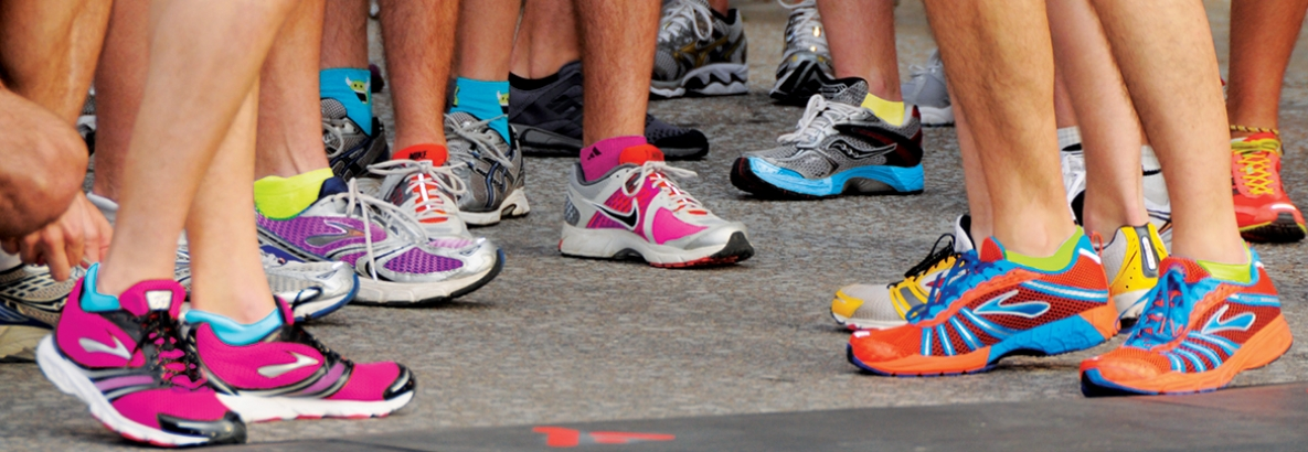 Multiple peoples' feet wearing running shoes