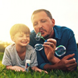 picture of father and son blowing bubbles
