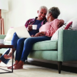 elderly couple talking on the couch